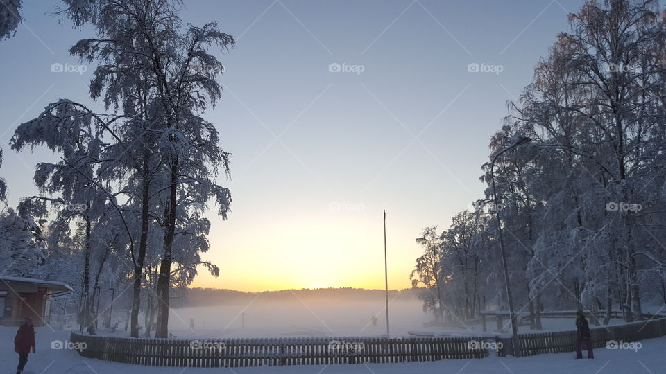 Snowy winter - sunset at the lake - mist