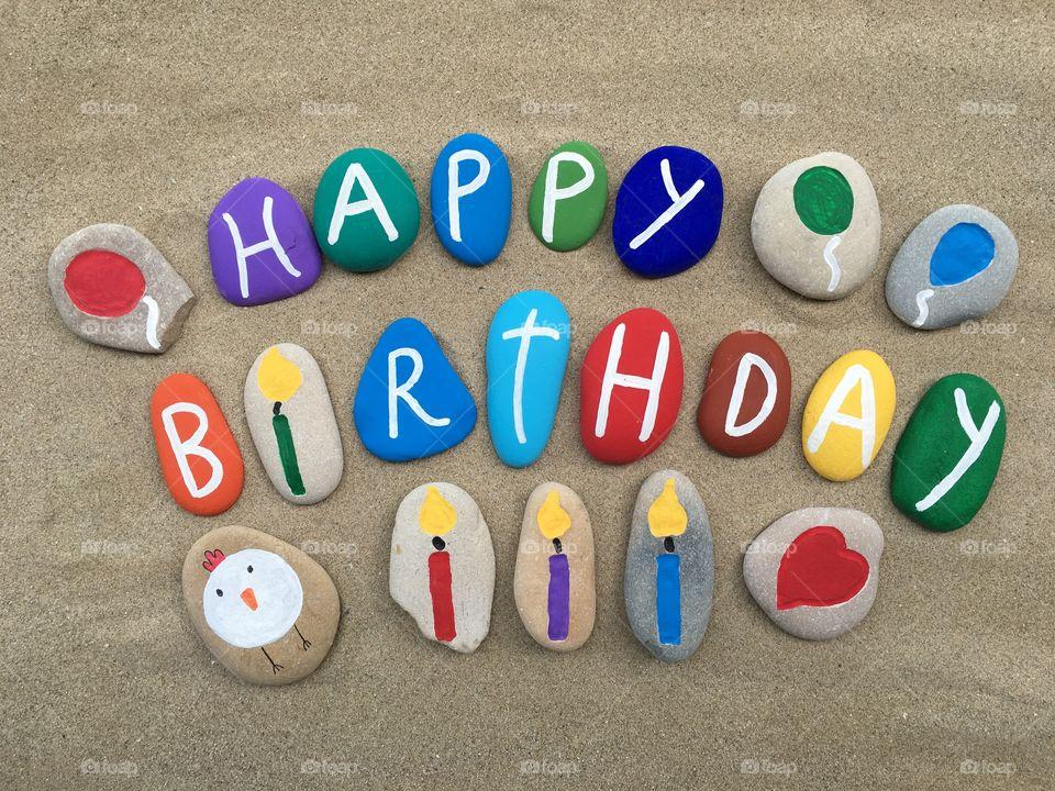 Happy Birthday, multicolored stones design on the sand