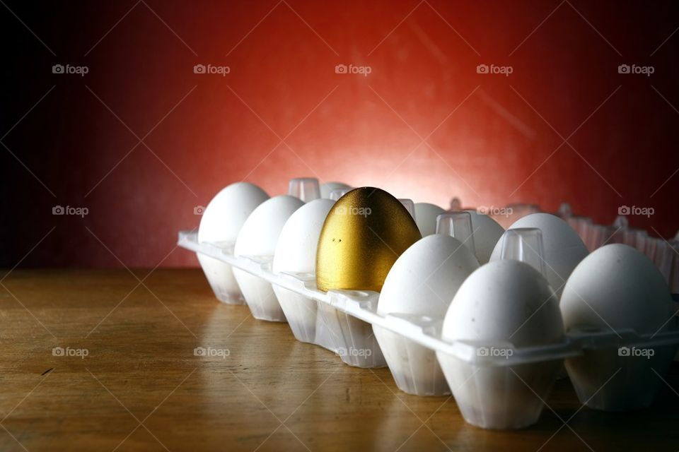 a golden egg among ordinary eggs in an egg tray