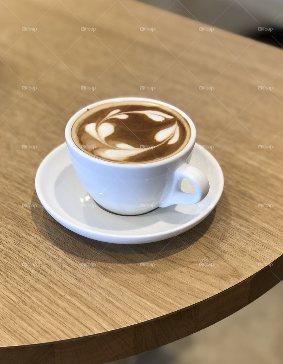 A cup of hot cappuccino and latte art