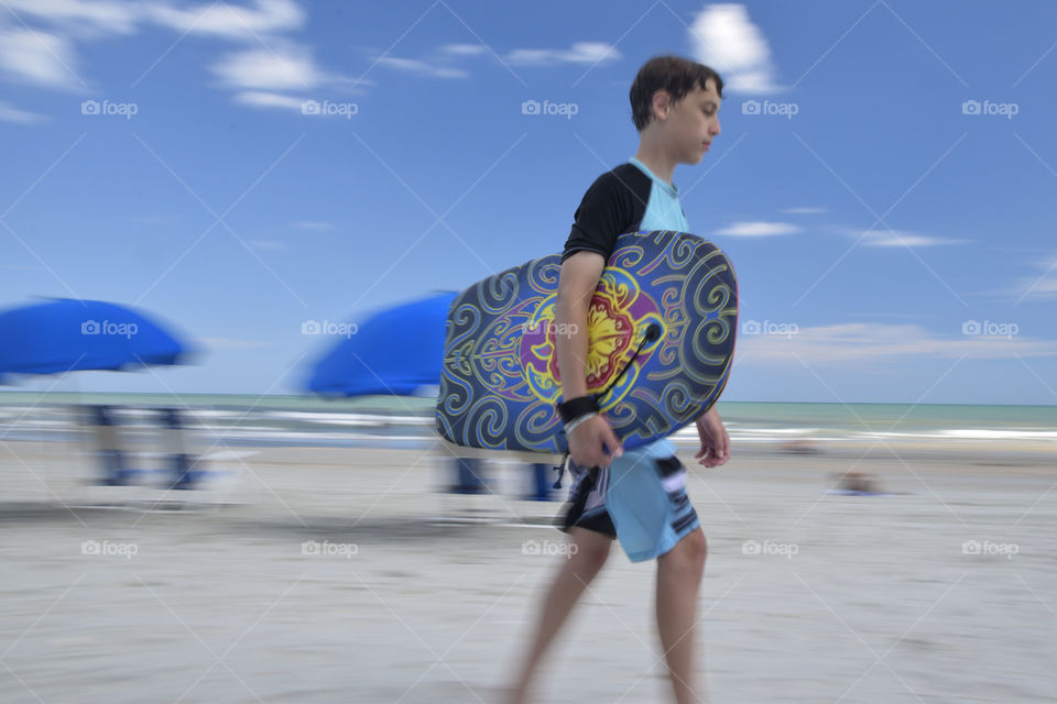 Boy walking with a Boogie Board on the beach