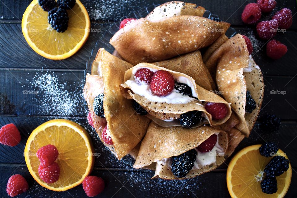 A plate of homemade cream and berry filled crepes on a dark wooden board with orange slices, raspberries and blackberries around it.