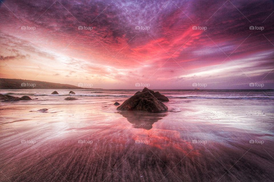 Red sky sunrise over a deserted beach in Cornwall, UK.