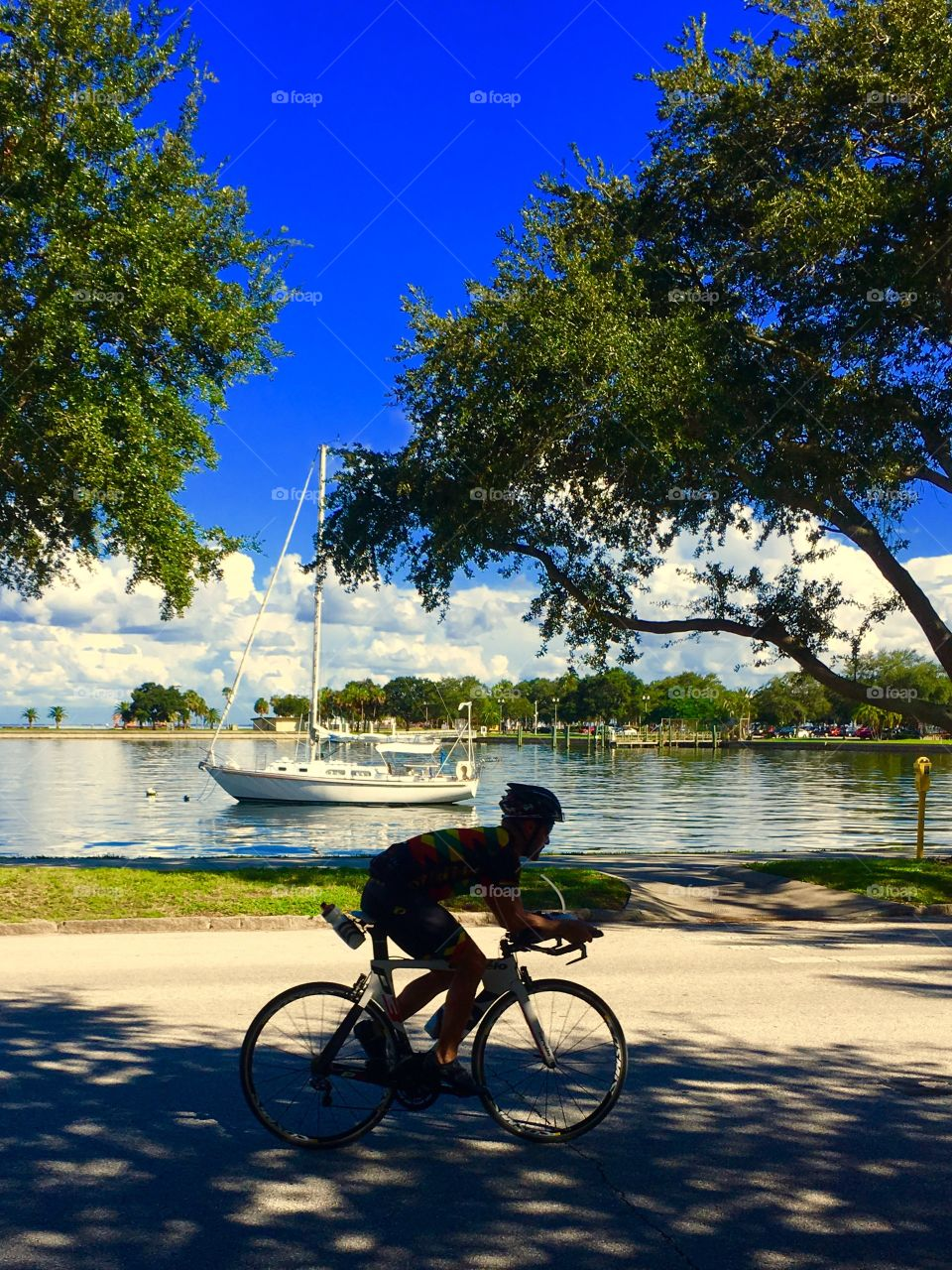 Bike rider and sailboat together