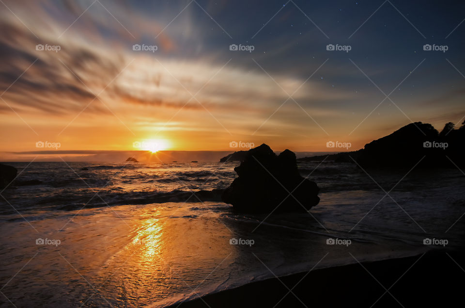 Silhouette of rock at beach during sunset