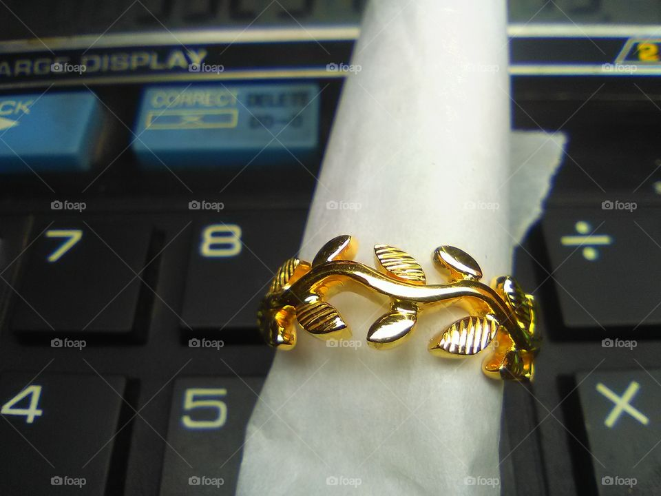 Close-up of gold ring on calculator