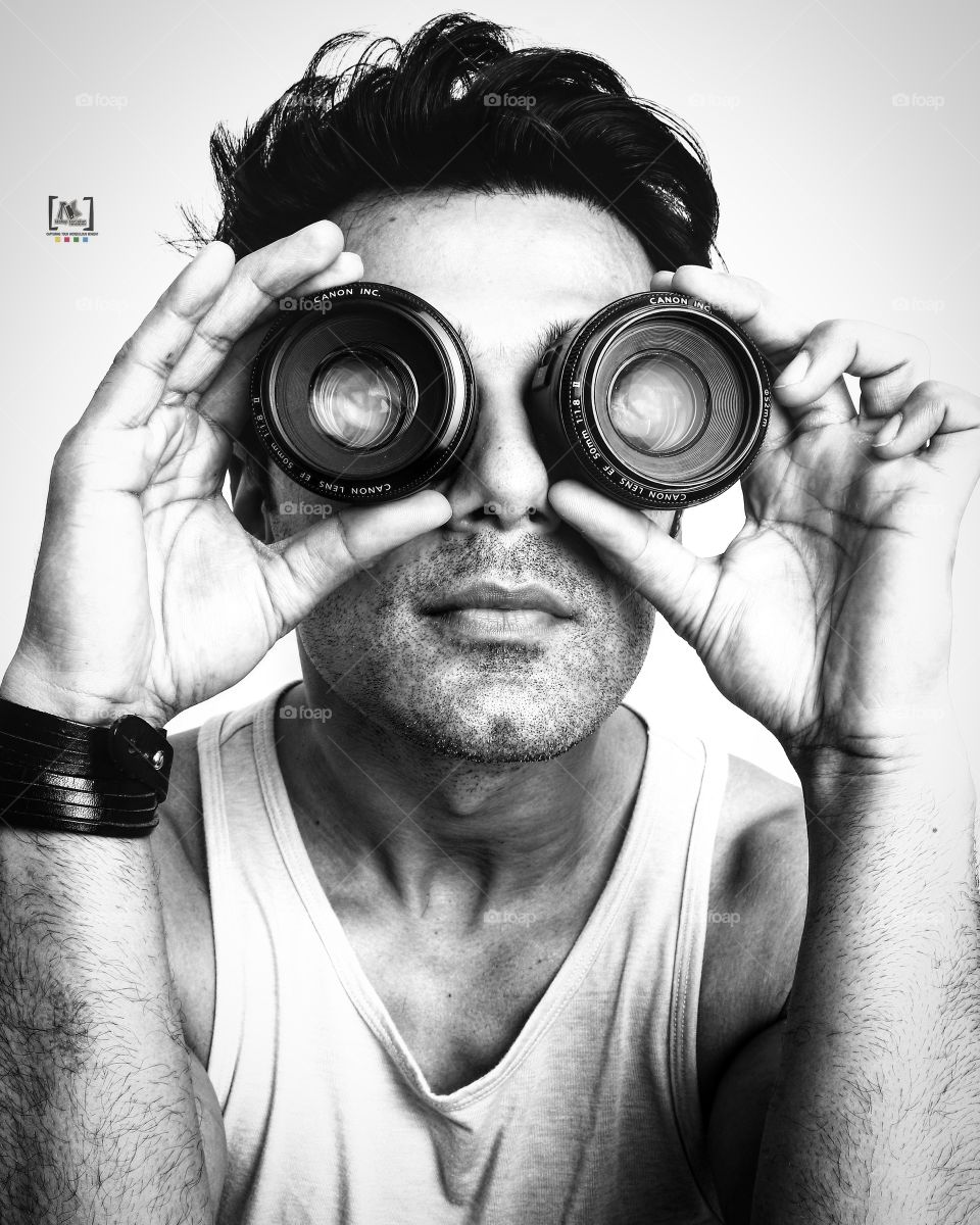 Man holding camera lens over the eyes