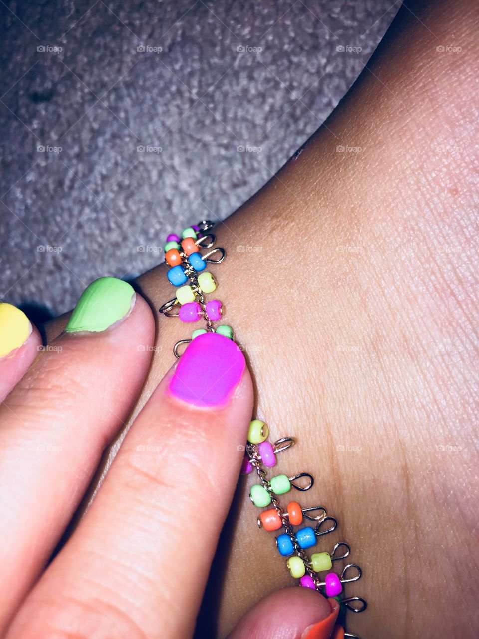 Colorful ankle bracket with neon nail polish