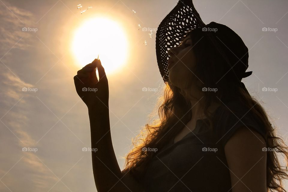 Woman holding toothpick in front of sunlight