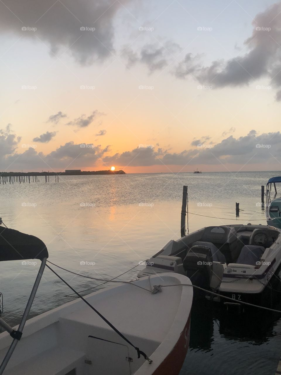 A view of an orange sunset from a boat at the dock on a Caribbean island