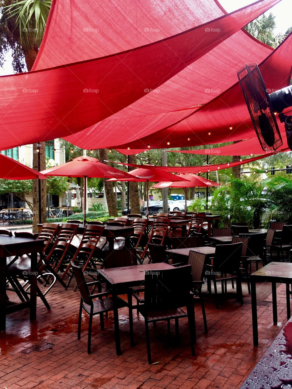 Sidewalk cafe with red shade sails and umbrellas