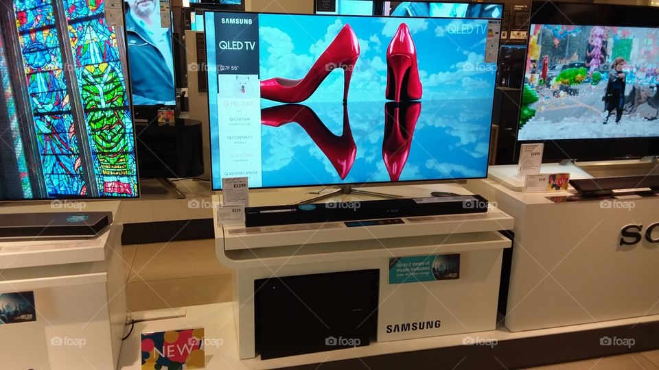Samsung QLED television 4K Ultra High Definition TV with forked style stand displayed with soundbar and sub-woofer
