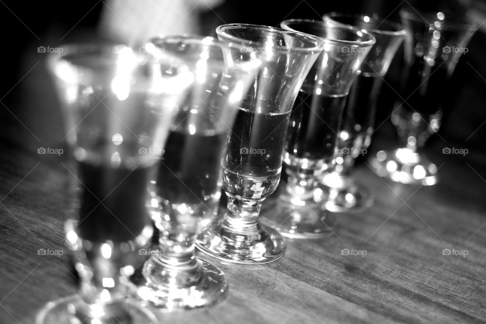 Six little shot glasses, standing in a row.  The party is underway. The glasses are filled with a dark drink. maybe Kahlúa? Maybe Port? Maybe Sambuca? Maybe even Jägermeister? Drink up!