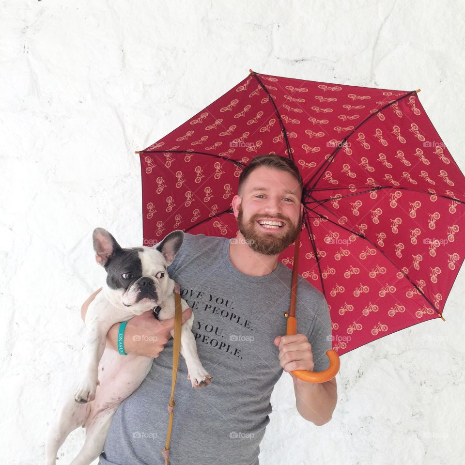 Love You Love People Umbrella Shot. Guy holding French bulldog with umbrella in front of white background