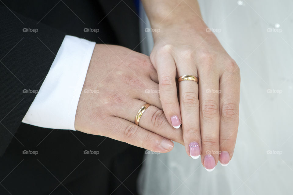 Young couple just married showing their rings with overlapping palms