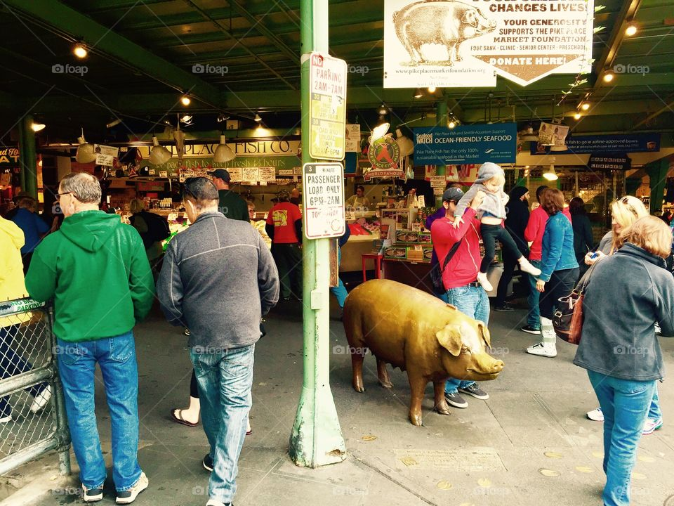 Pike Place Market Pig with father placing child on Pig
