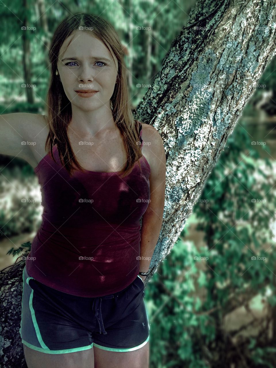 Sad teenage girl standing in front of tree