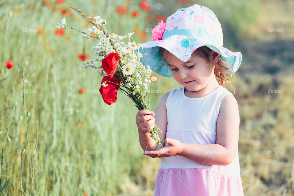 Lovely little girl in the field of wild flowers. Cute girl picking the spring flowers for her mom for Mother's Day in the meadow. Girl holding bouquet of flowers. Spending time close to nature