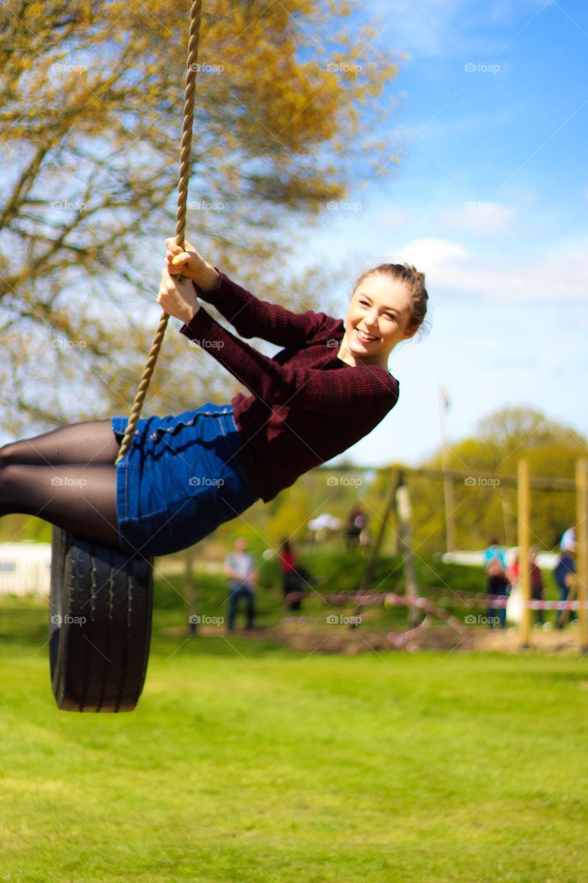 Young woman enjoying on rope swing