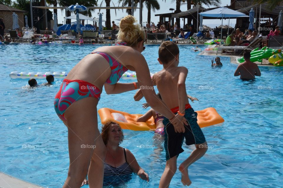 Woman pushing her child in swimming pool