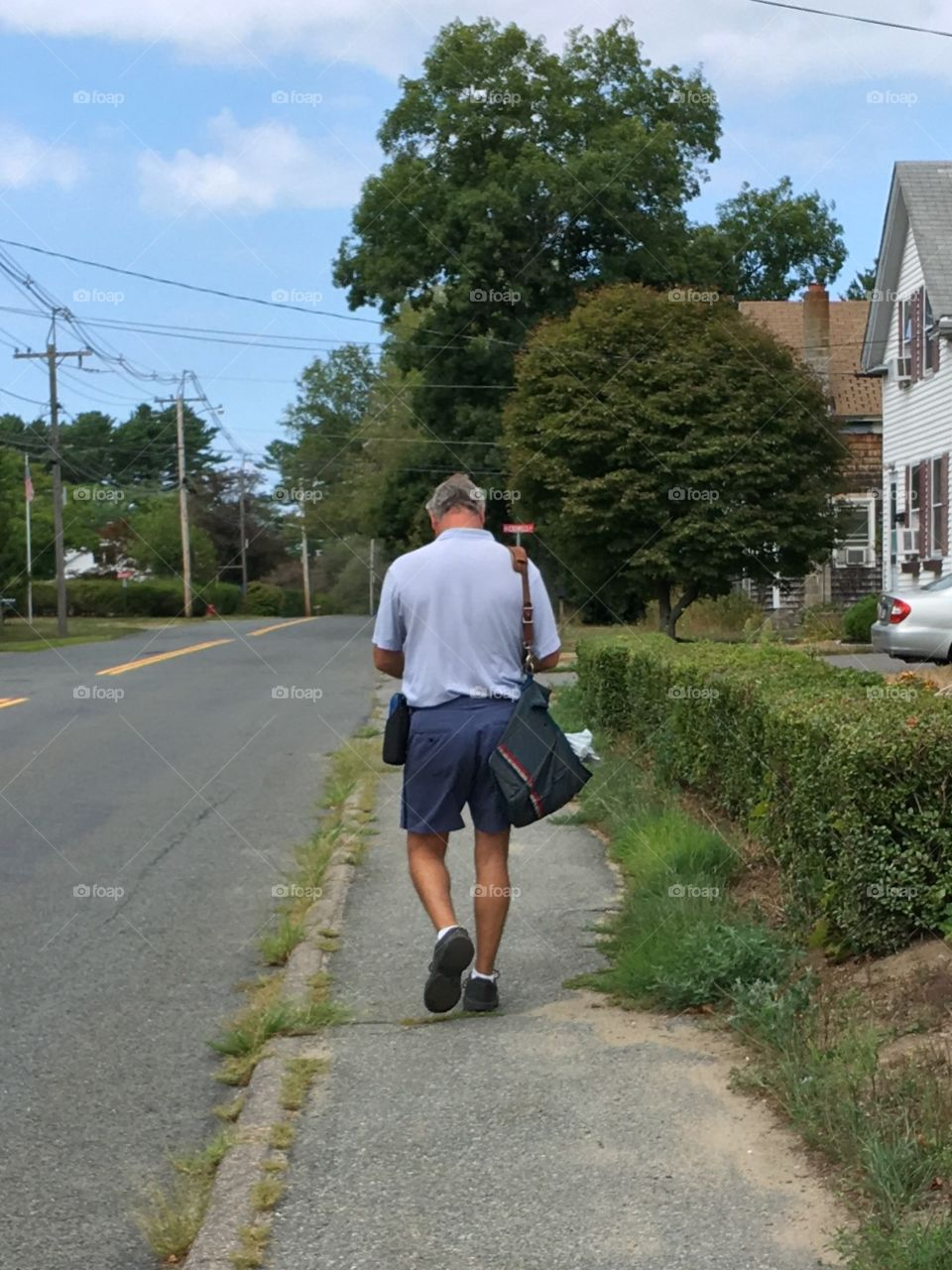 US Postal Service delivering mail to homes while walking.
