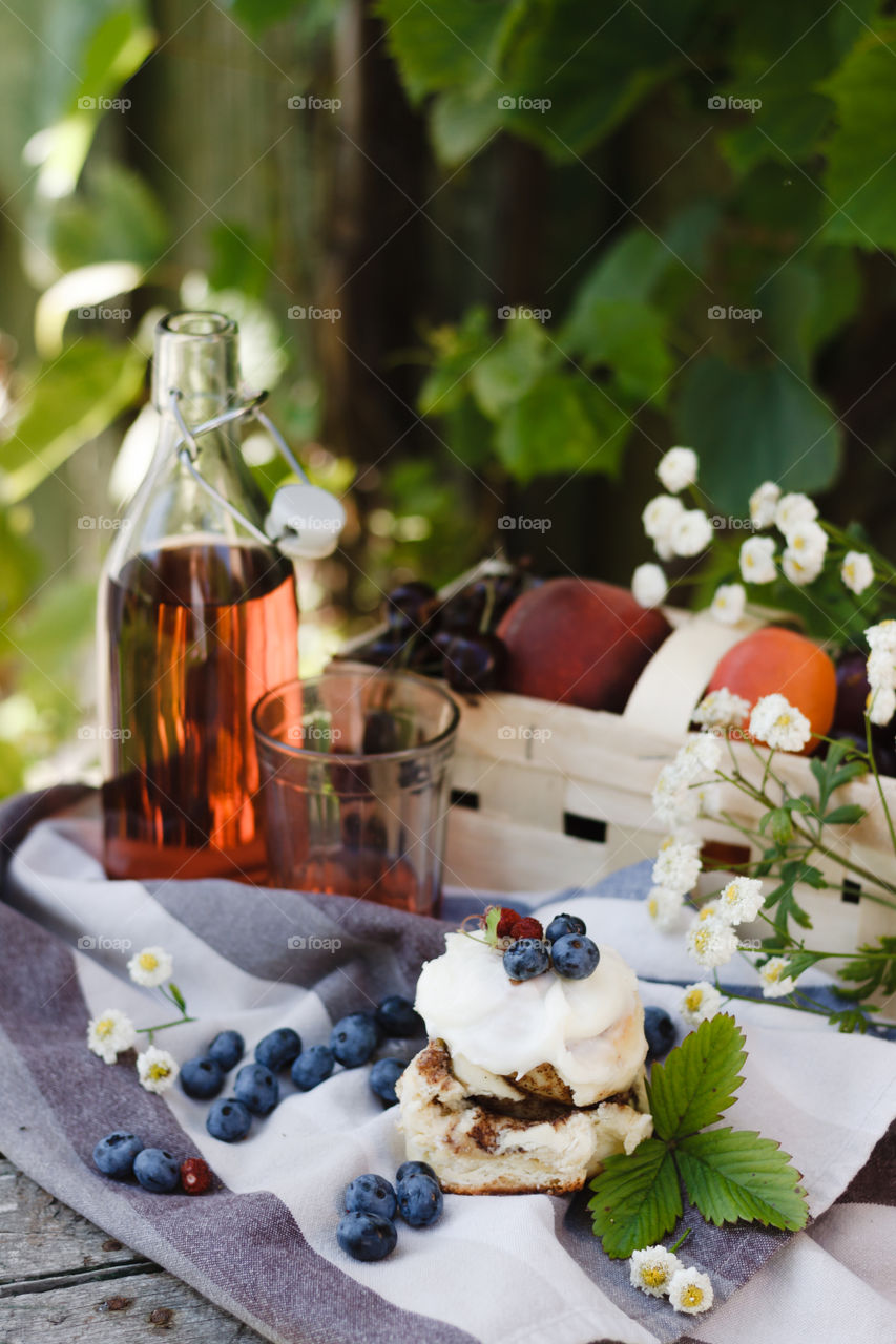 Cherry, apricot, plums, pink flowers and a berry cake in a summer garden