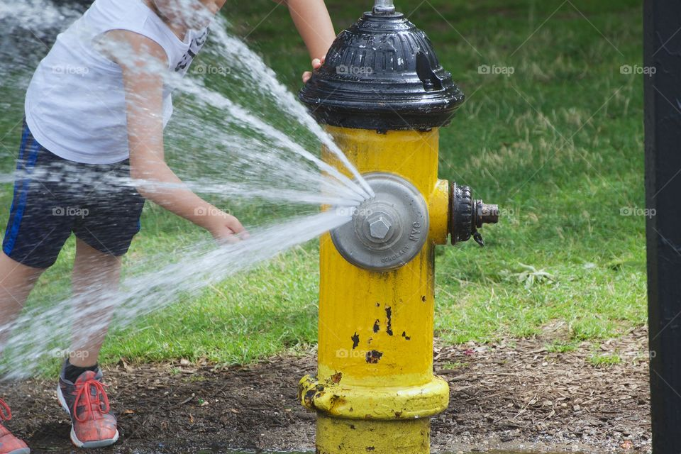 A boy in a New York City  park cooling off from the water flowing out of an open fire hydrant.
