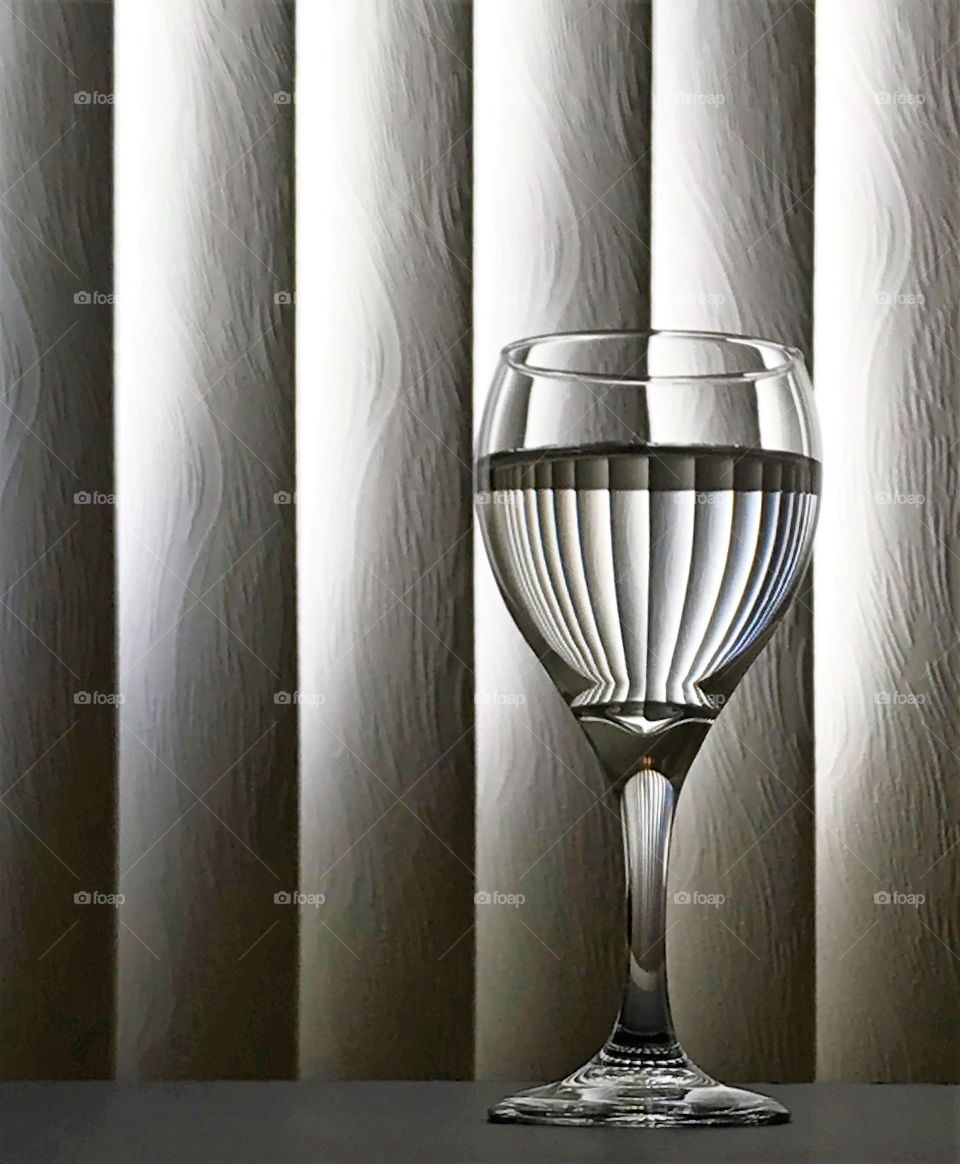 Wine glass with vertical blinds reflecting into the partially filled glass