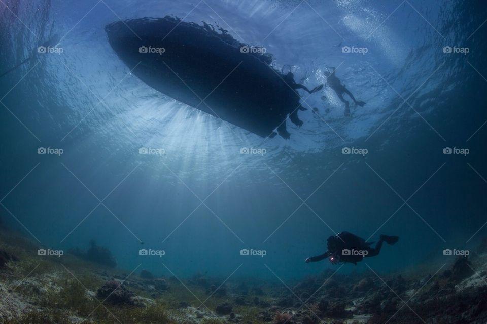 Diver under a boat silhouette