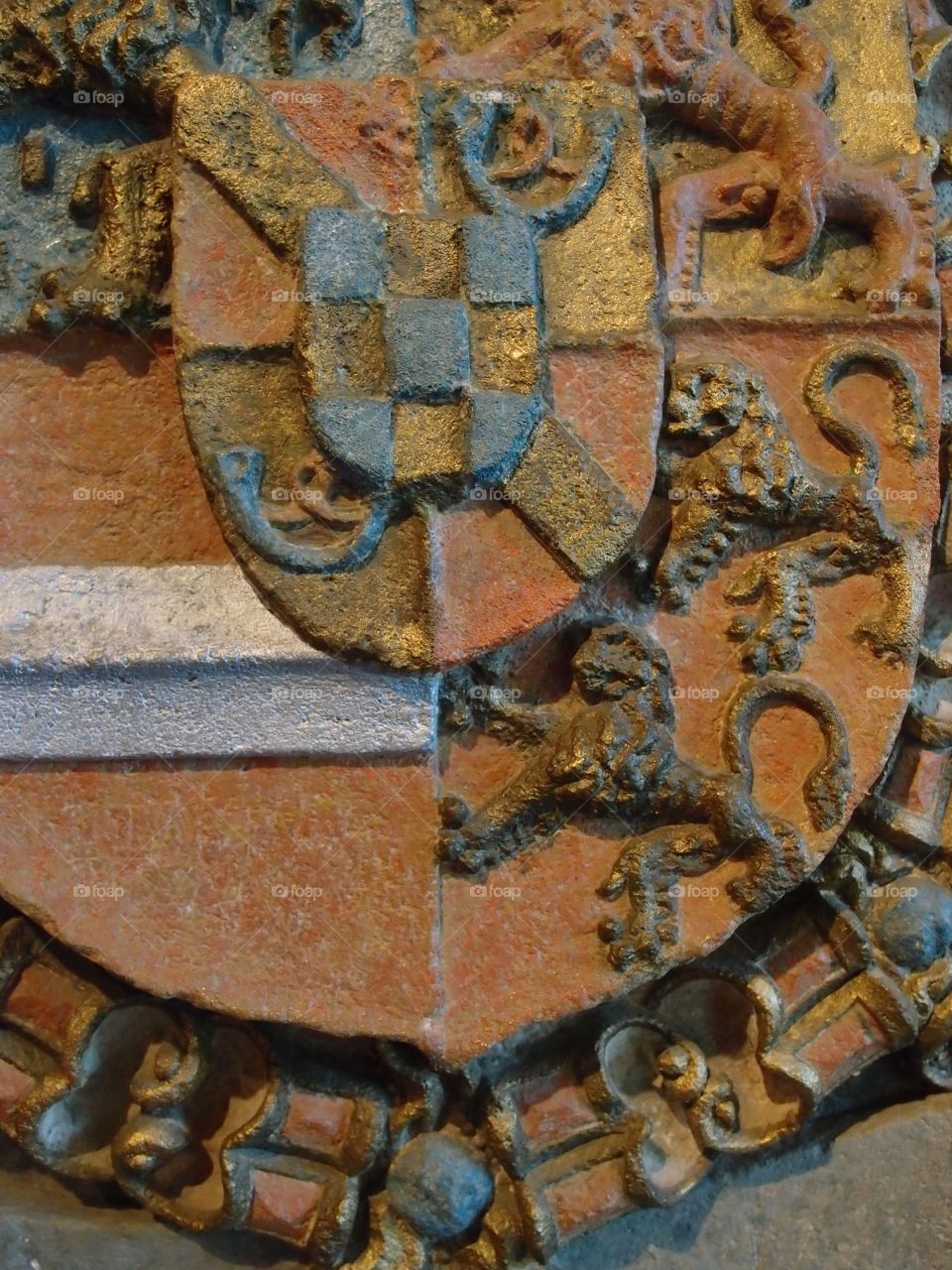 A decorative family crest with decorative lions and a patterned shield in the Chateau dé Vianden in Northern Luxembourg.