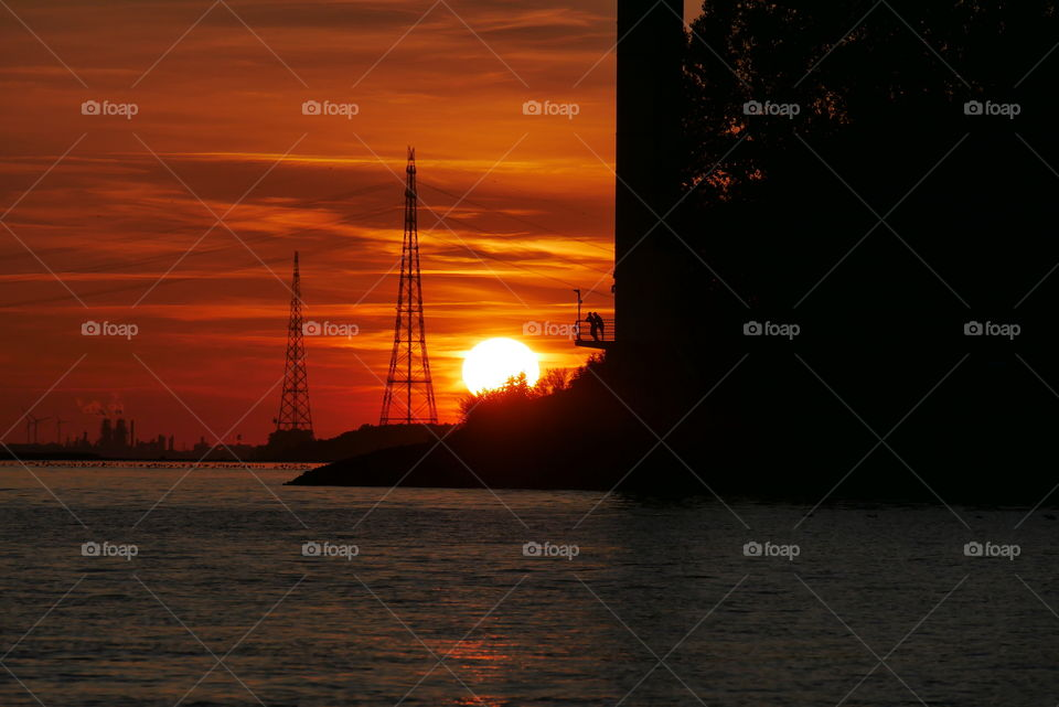 Sunset - on the river Elbe in Schleswig Holstein Germany - Two people enjoy the beautiful sunset from the platform of a tower