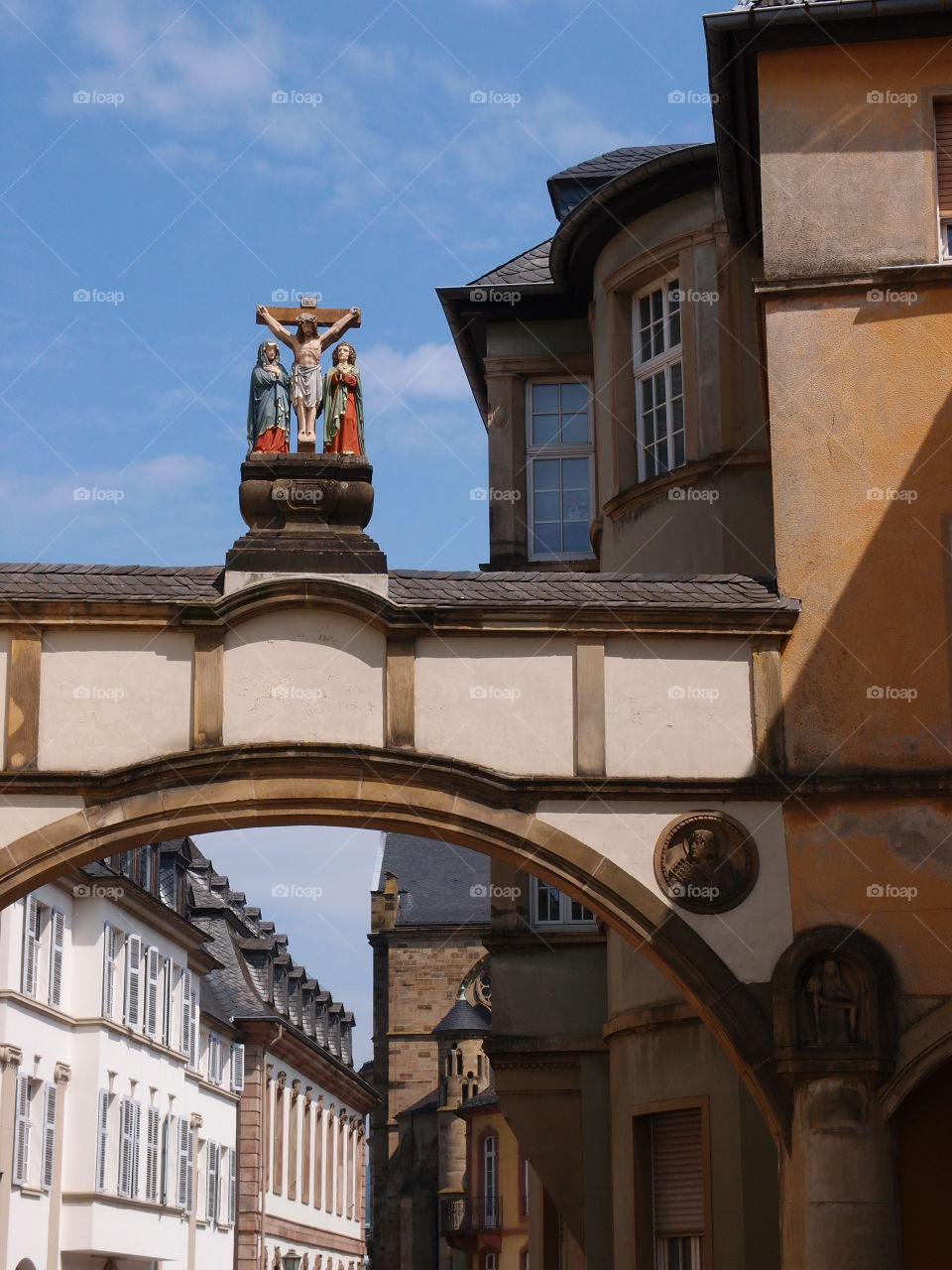 A statue of a crucified Jesus on top of a beautiful arch all against a bright blue sky in Europe on a sunny summer day.