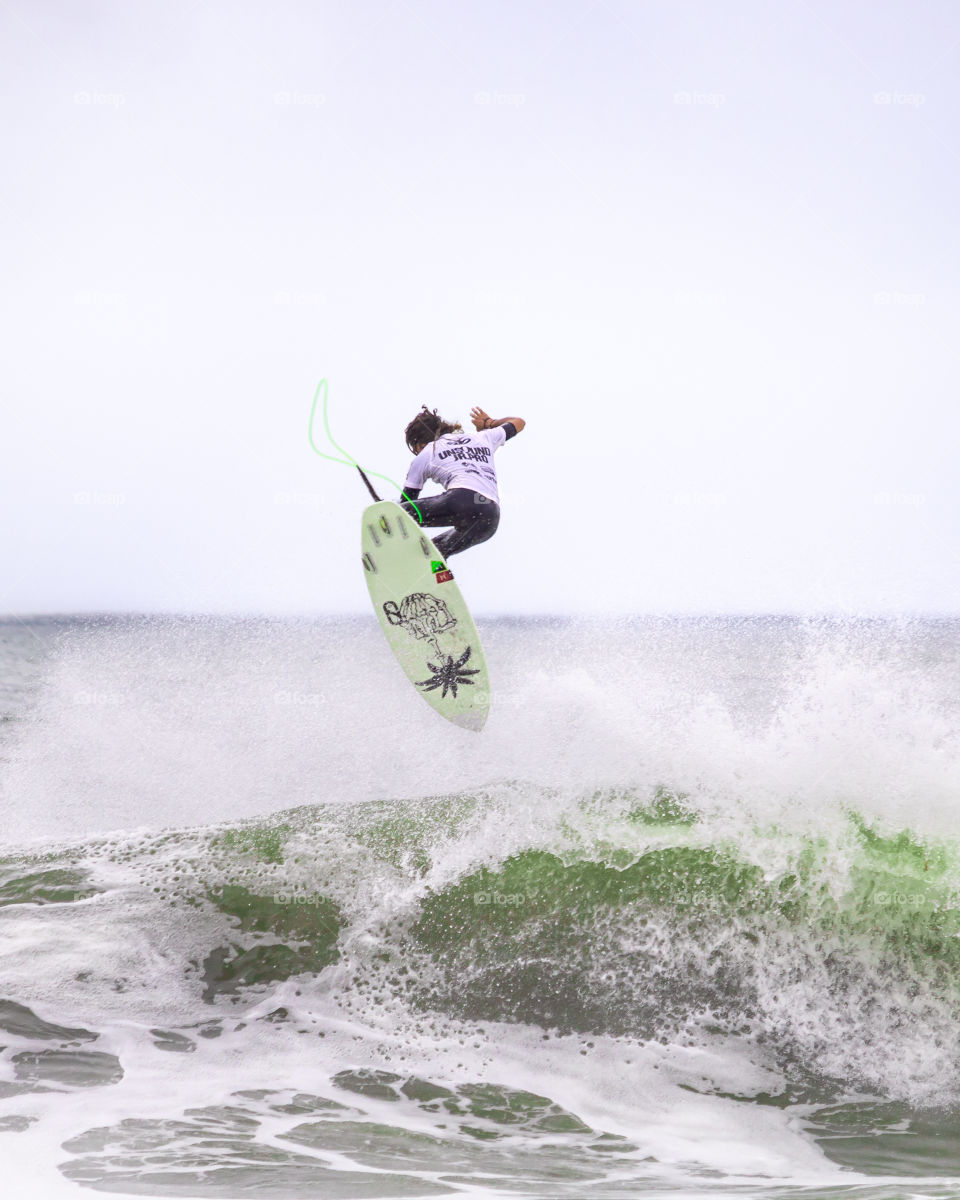 A surfer in the ocean pulling an impressive big aerial trick off of a large wave.