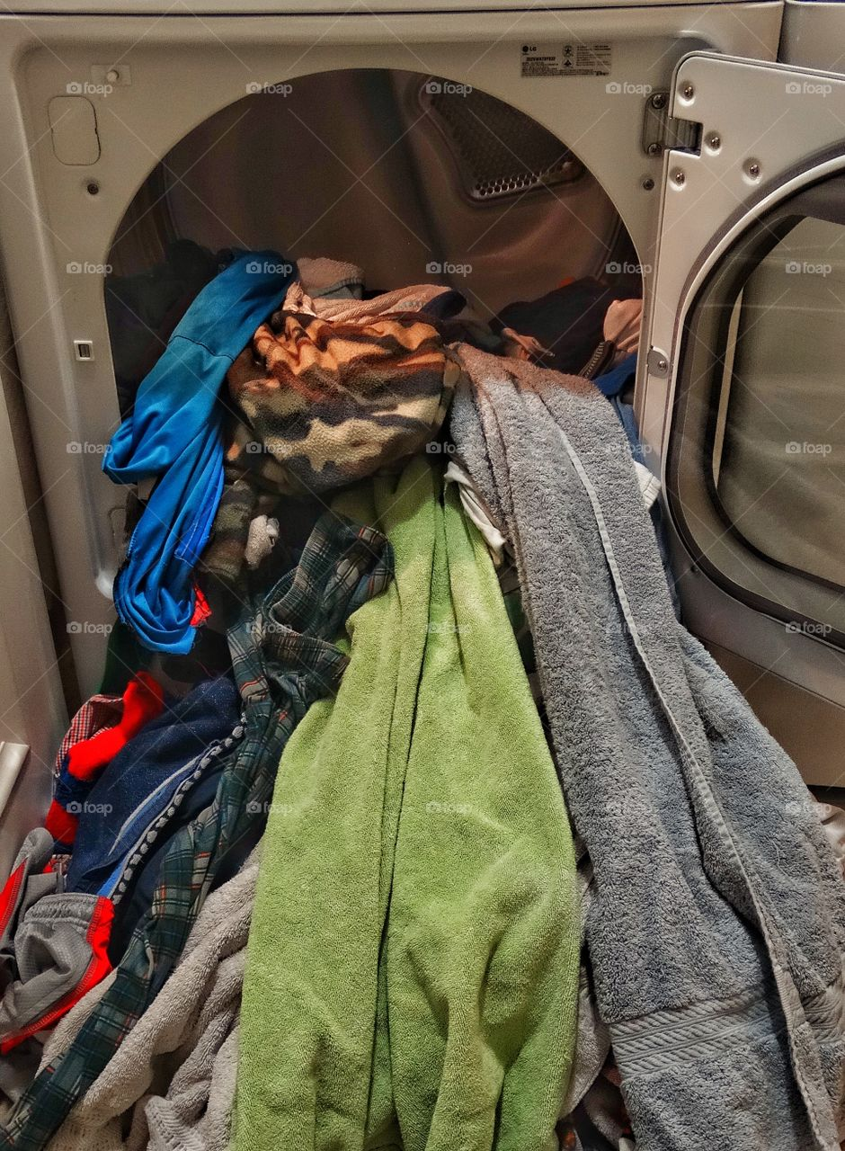 Too Much Laundry. Laundry Spilling Out Of A Clothes Dryer