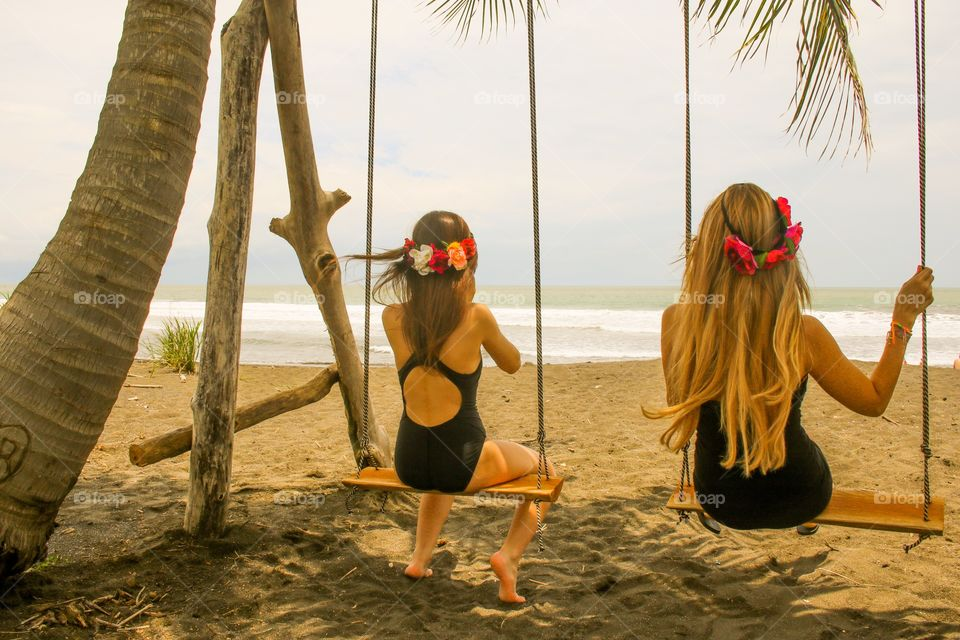 Two girls on swings on the beach