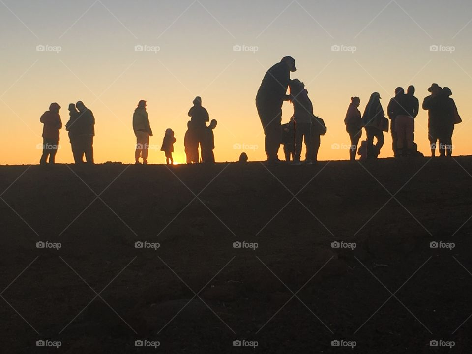 A group of people gathered together silhouetted by the sunset they are watching.