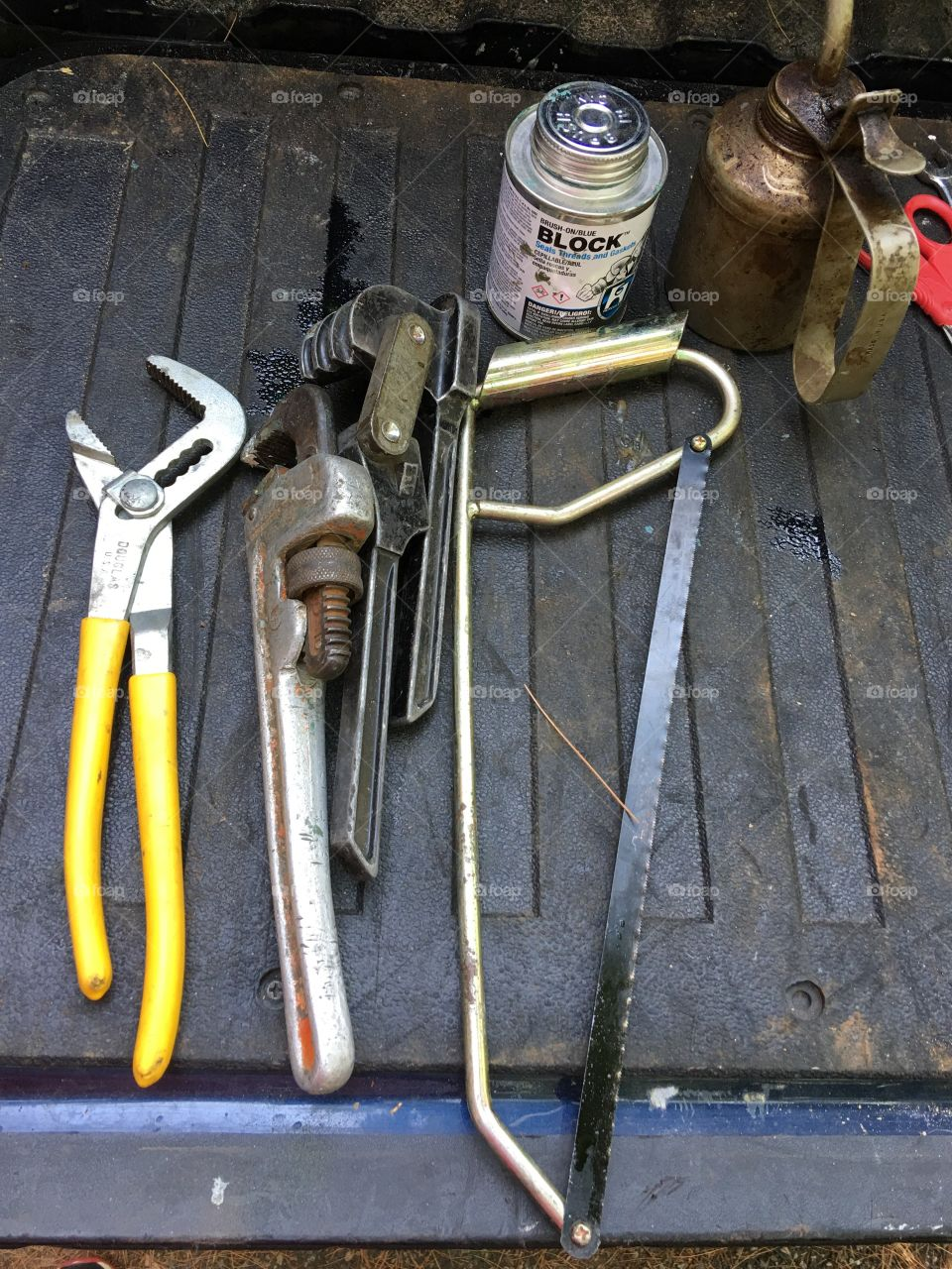 Layout of plumbers tools. Wrenches, solder, hand saw, glue pvc pipes, etc.