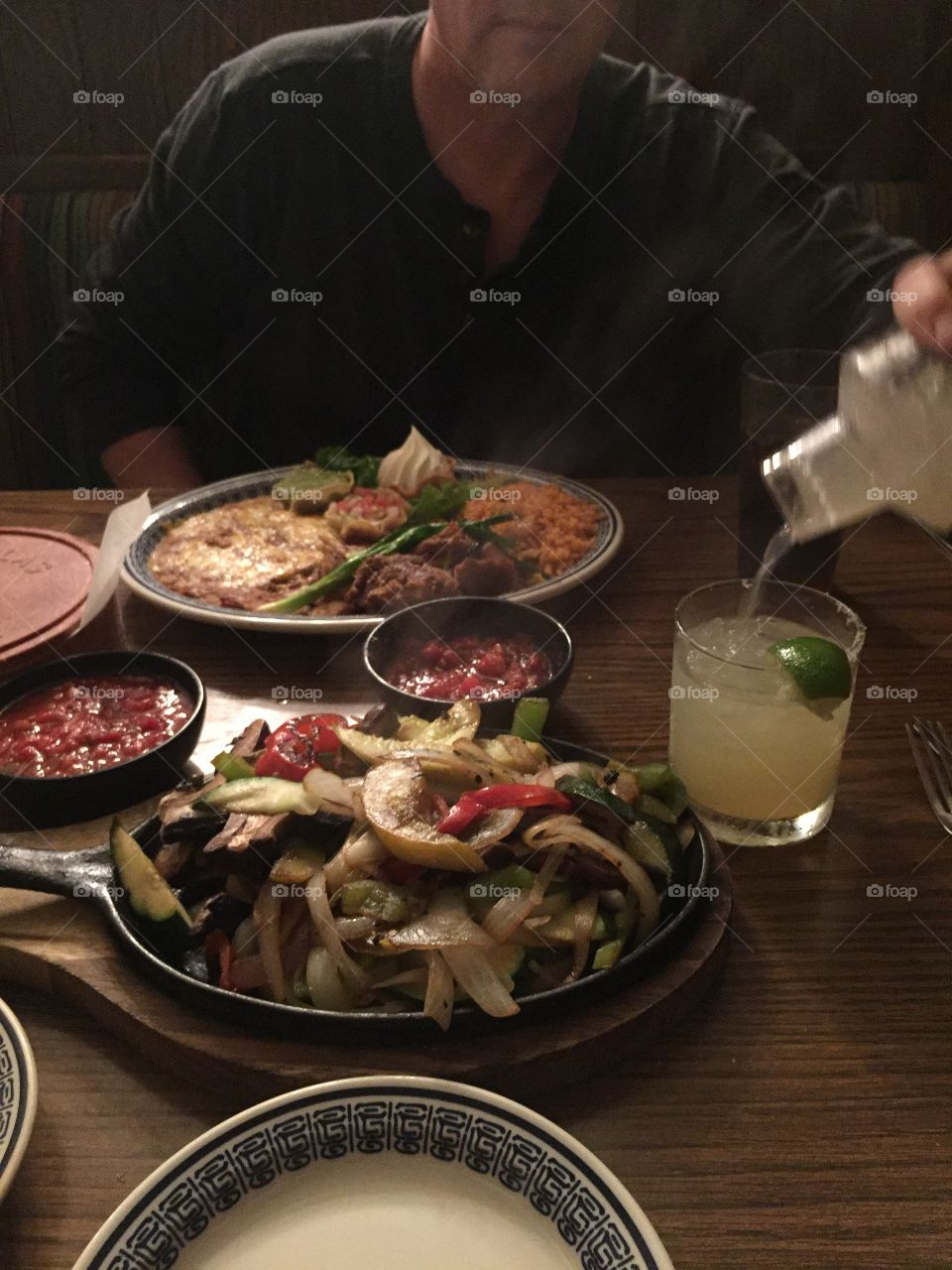 Restaurant table for two for warm romantic dinner featuring Mexican fajitas, chips, salsa, rice, refried beans, cheese, lime, salt, margarita, cilantro