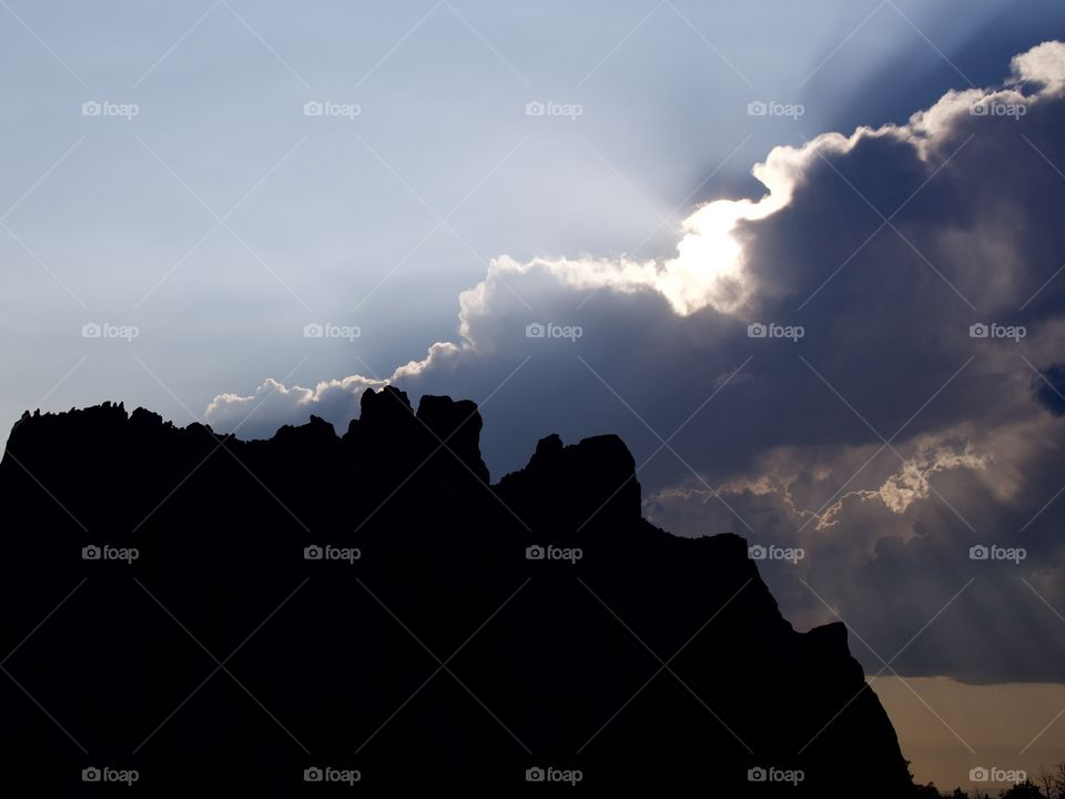 Beautiful sun rays break through the clouds after an evening summer rain storm at Smith Rocks in Central Oregon.