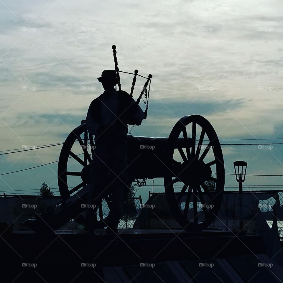 actual person playing the bagpipes on a war memorial in New Orleans.