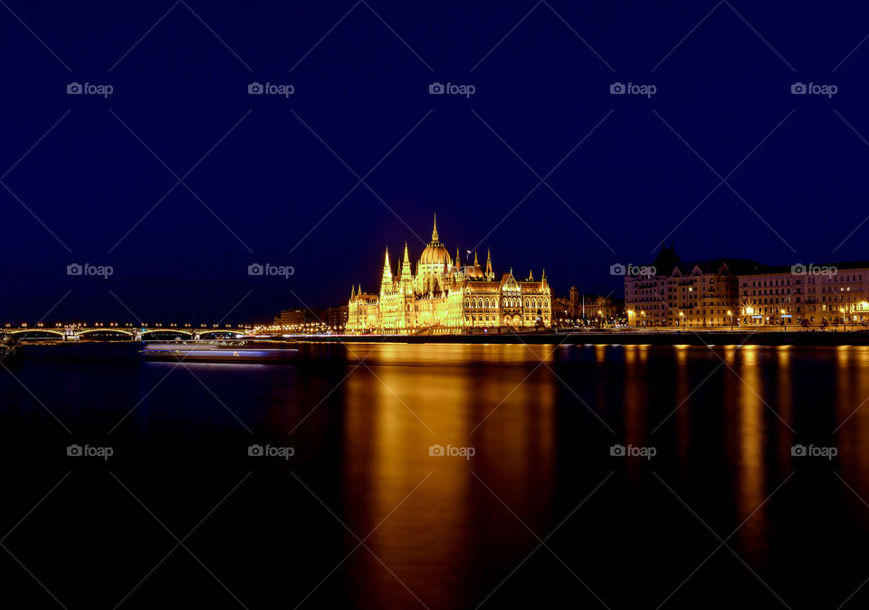 Budapest parliament by Danube river at night