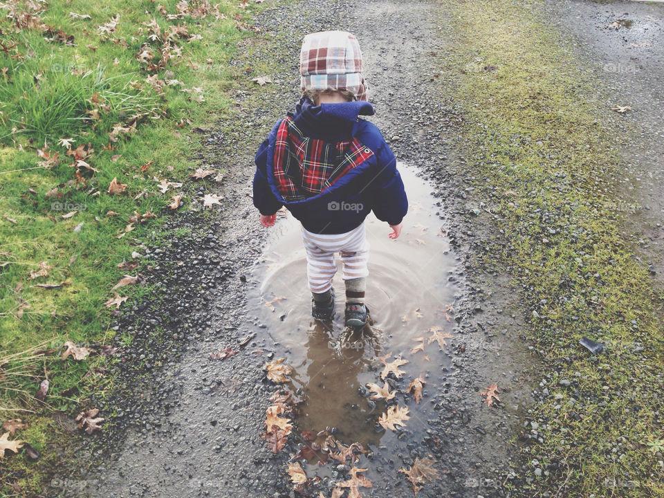 Little Boy Walking Through Puddle