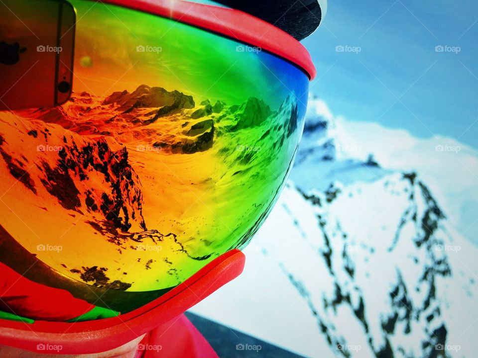 Snowcapped mountains reflected in goggle